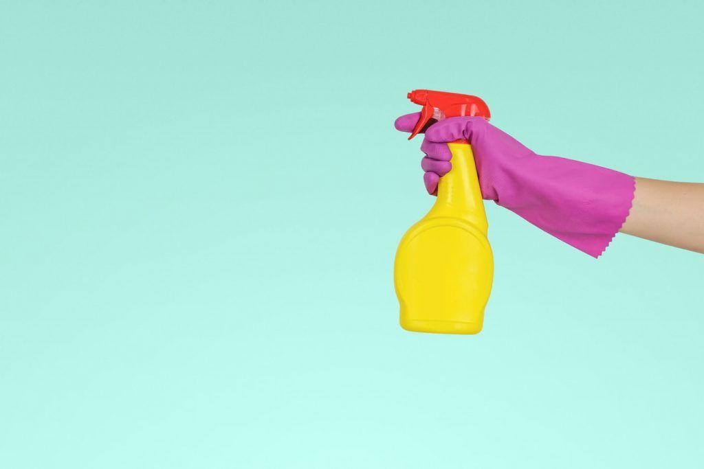 Bild som illustrerar en rengöringsspray med en hand som har en gummihandske på. En illustrerande bild till en guide om hur man rengör och städar ett tangentbord bäst.