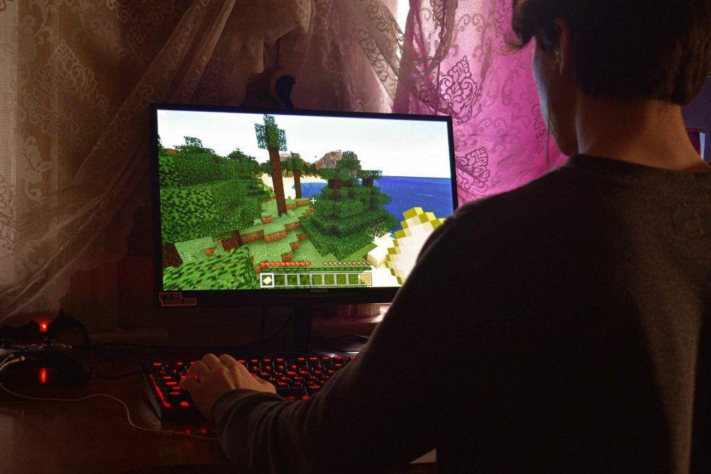 En kille som spelar Minecraft. Han sitter ergonomiskt och bra för kroppen, vilket är viktigt när man spelar. Så att kroppen inte får ont.