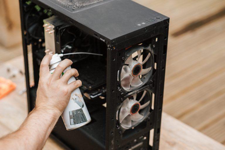 Bild på någon som rengör datorn invändigt från damm med hjälp av tryckluft.