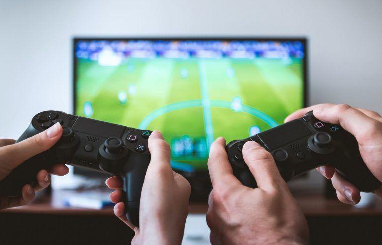 Två personer som spelar Playstation på en gaming-TV. Förmodligen njuter de av att spela på en riktigt bra spel-TV som är snabb och skarp i bilden.